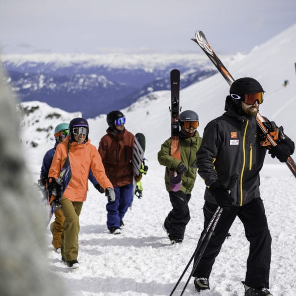 Friends skiing and snowboarding with a Mountain Host in Whistler
